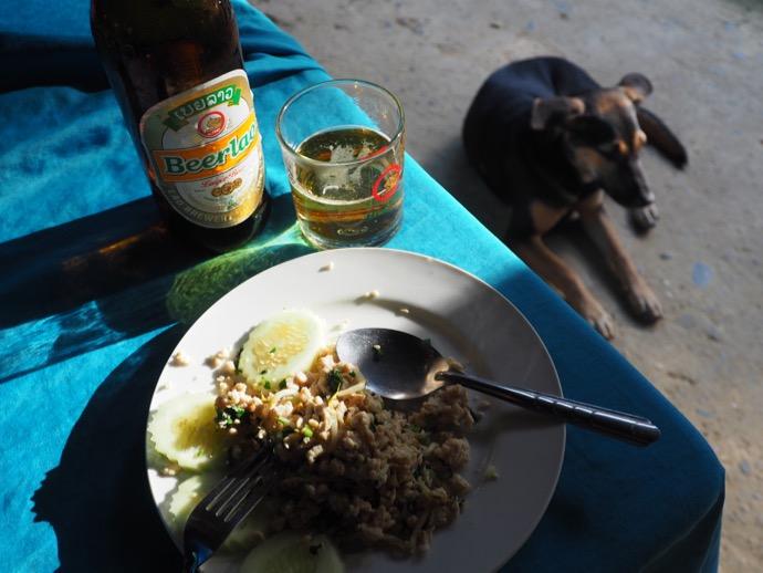 ラープを食べている横に座る黒い犬
