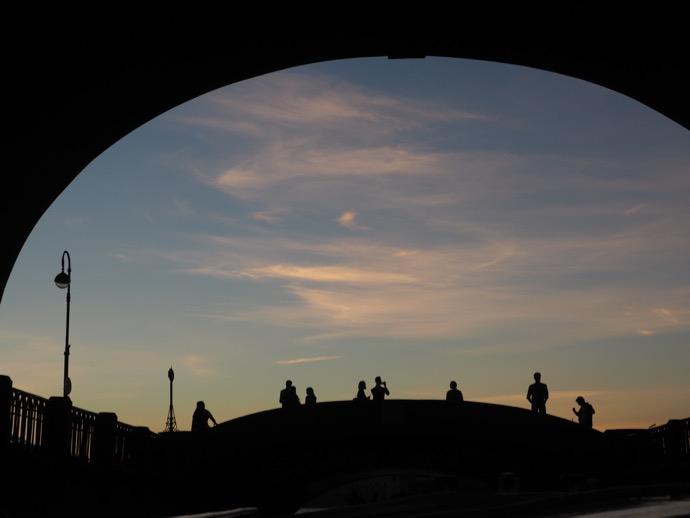 夕暮れ時の橋の人々