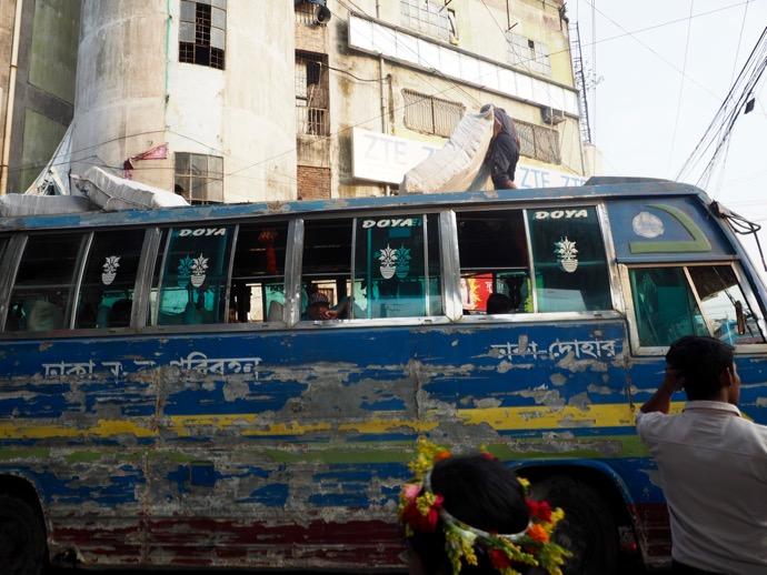 バスの屋根からマットレスを運ぶ男性