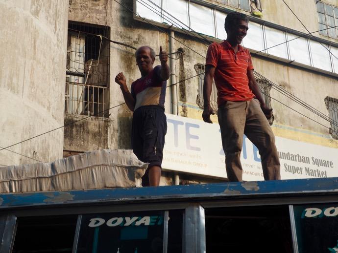 バスのうえでポーズを決める男性
