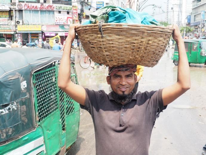 カゴを頭に乗せて運ぶ男性