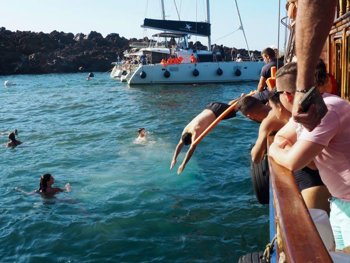 船から温泉へとダイブする男性