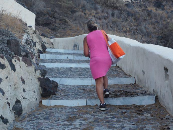 階段を上るピンクのワンピースの女性
