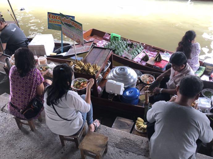 ボートでローカルフードを買ってその場で食べる人たち
