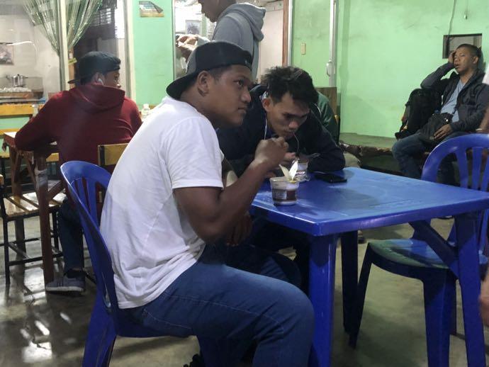 サービスエリアでカップラーメンを食べる男性