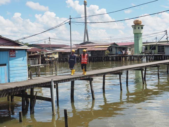 水上集落を歩く工事作業員男性