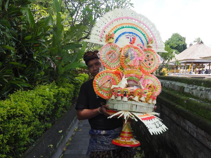 タマン・アユン寺院で飾りを運ぶ男性