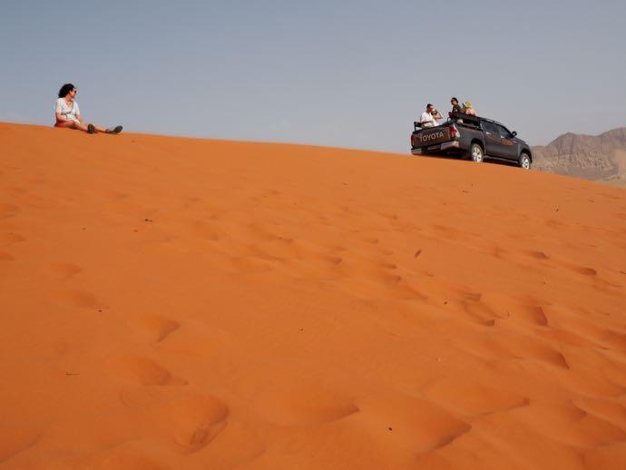 紅い砂丘に座る女性