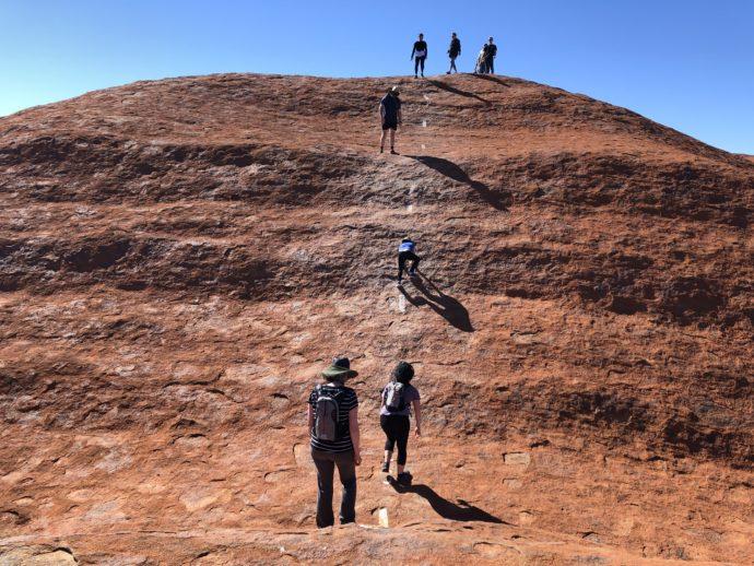 ウルルの岩肌をよじ登る
