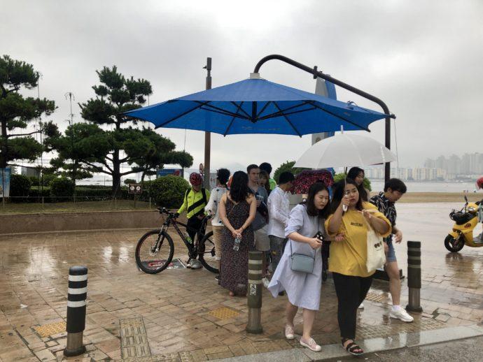 ゲリラ豪雨で雨宿りする人々