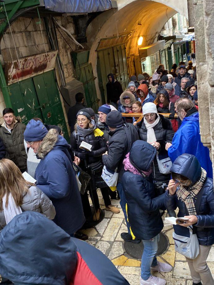 十字架を背負いながらヴィアドロローサを歩く観光客