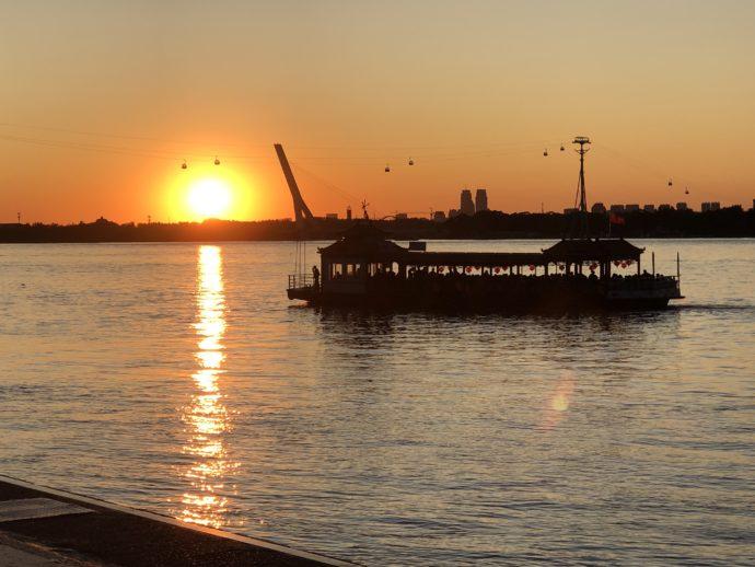 松花江に沈む真っ赤な太陽と船