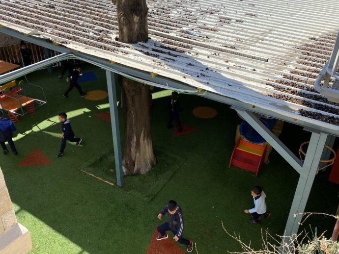 屋根の下で遊ぶ子供達