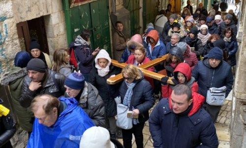 十字架を背負いながらヴィアドロローサを歩く信者
