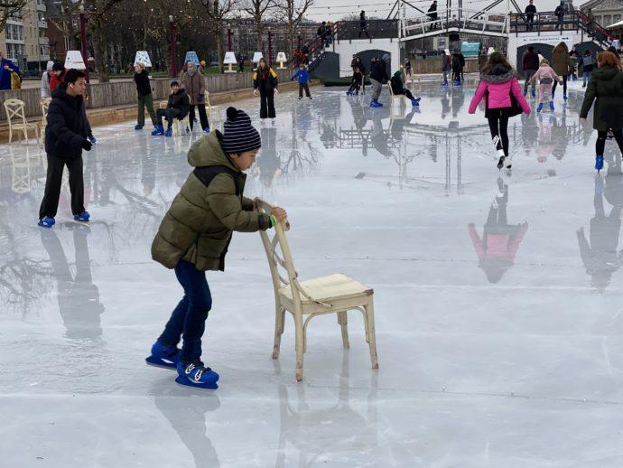 スケートリンクで椅子を支えにする子