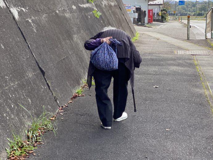 杖をついてゆっくり歩く女性
