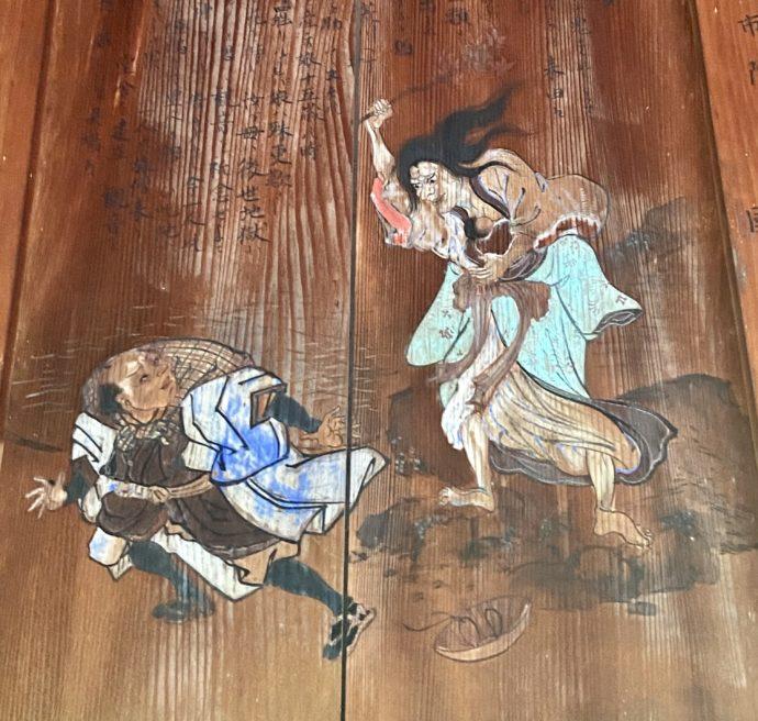怒る女性と男性の板絵