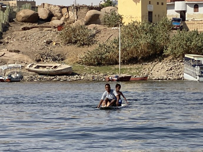 手漕ぎボートでナイル川を渡る少年たち