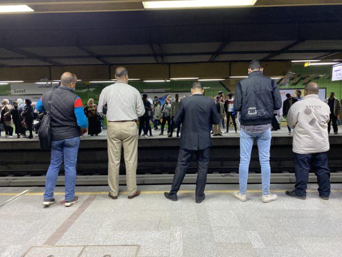 並んで電車を待つ男性