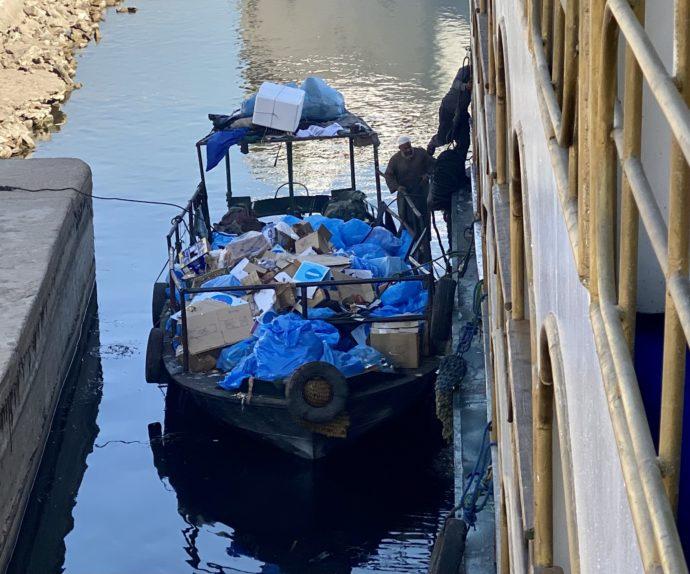 クルーズ船から小舟にゴミを積む