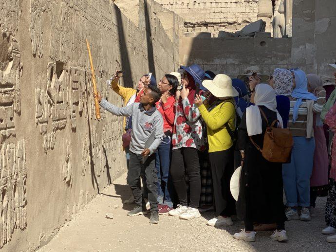 ルクソール神殿のレリーフを見る観光客