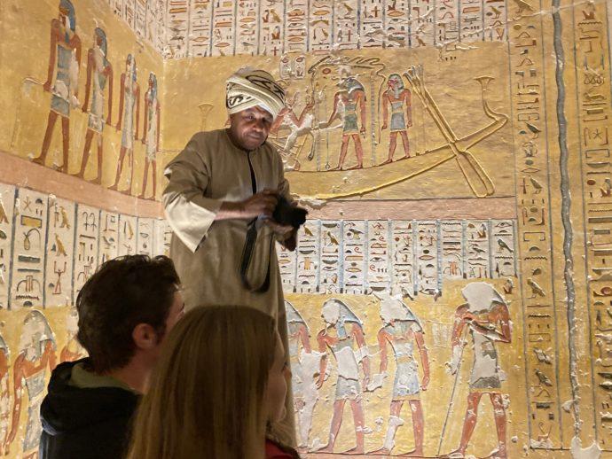 ラムセス4世の墓の壁画と写真撮影するエジプト人