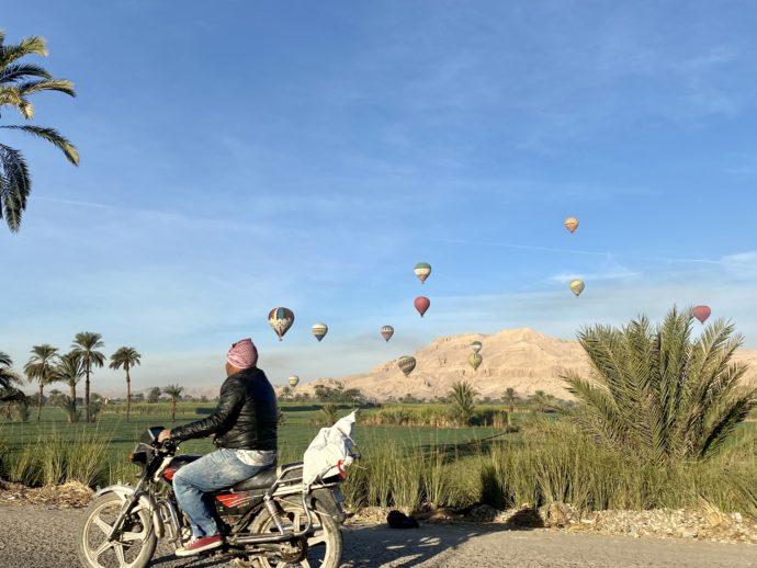 ルクソール西岸に浮かぶ熱気球とバイク